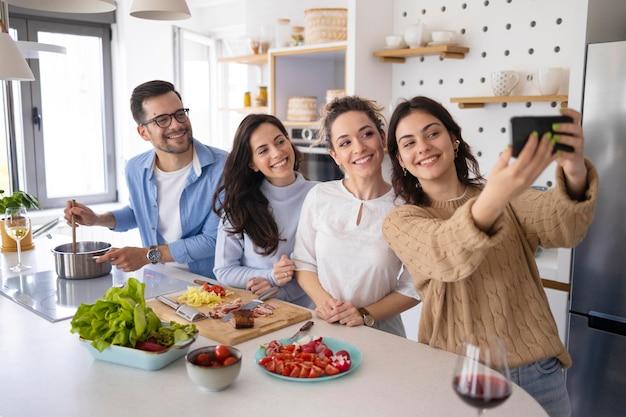 Groep vrienden die een selfie in de keuken nemen