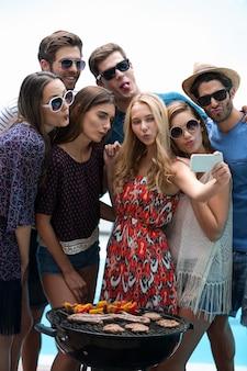 Groep vrienden die een selfie nemen dichtbij pool