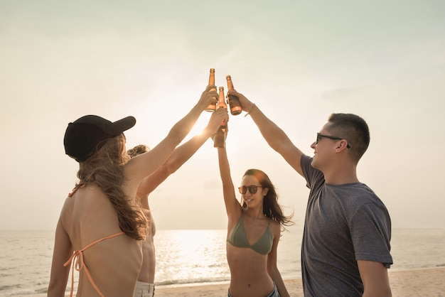 Groep vrienden die en bij het strand in schemering vieren drinken