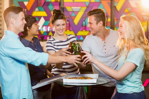 Groep vrienden die fles bier roosteren