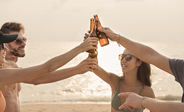Groep vrienden die flessen van het partij claging bier hebben bij het strand