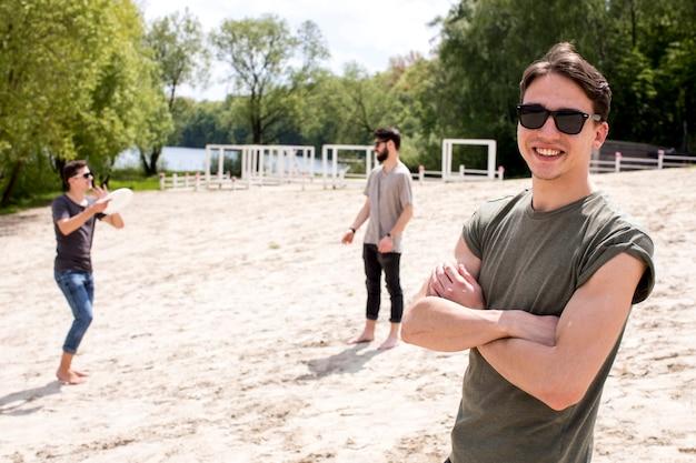 Groep vrienden die frisbee op strand spelen