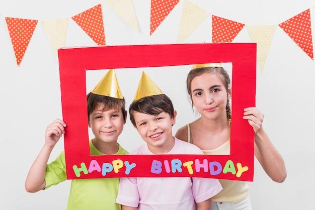 Groep vrienden die gelukkig verjaardagskader houden die partijhoed dragen