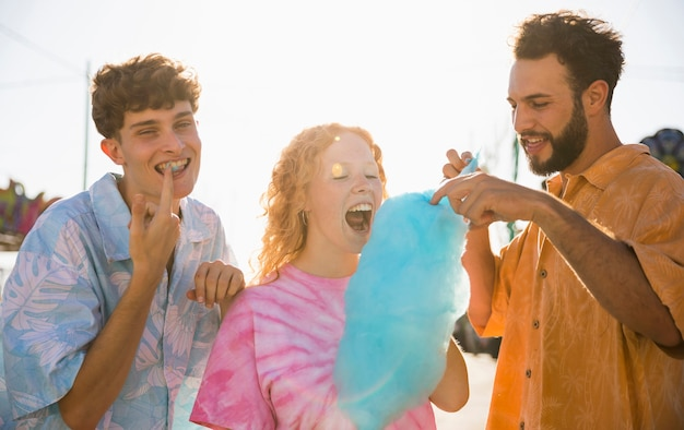 Groep vrienden die gesponnen suiker eten