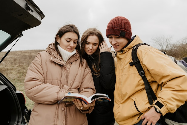 Groep vrienden die gidsboek raadplegen