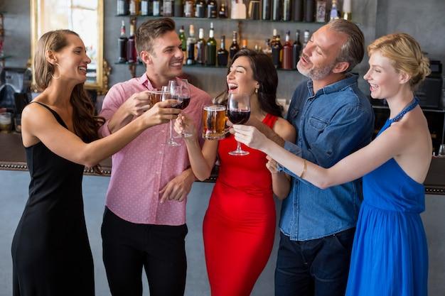 Groep vrienden die glazen bier en wijn roosteren