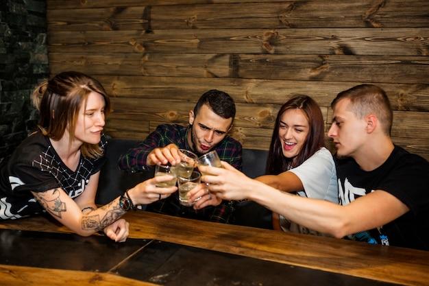 Groep vrienden die glazen dranken roosteren bij bar