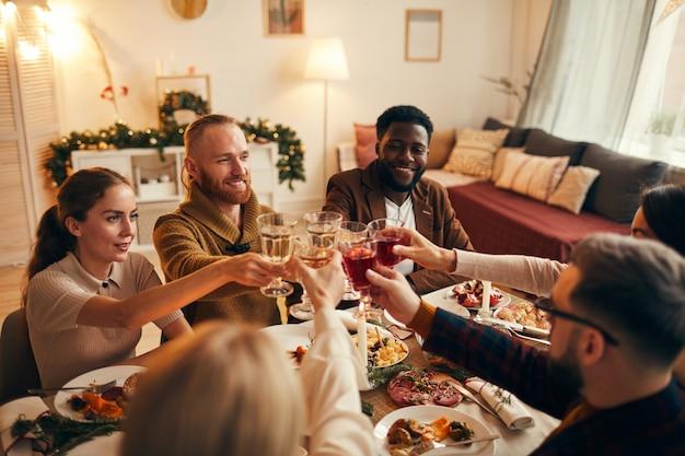 Groep vrienden die glazen opheffen bij dinerpartij