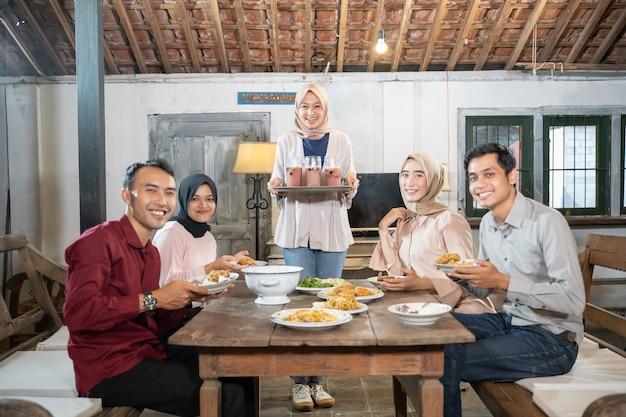 Groep vrienden die glimlachen terwijl ze samenkomen wanneer ze samen vasten in de eetkamer