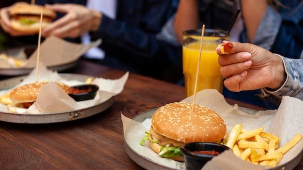 Groep vrienden die hamburger met gebraden gerechten hebben