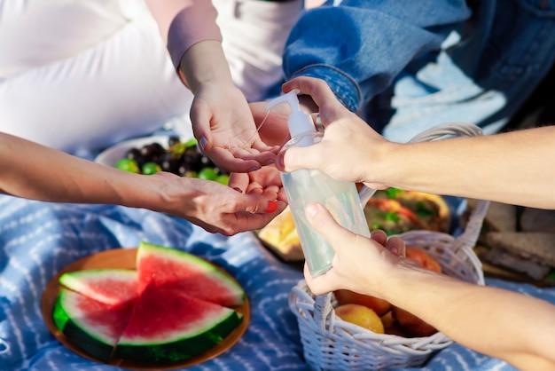 Groep vrienden die handen desinfecteren bij een picknick met lekkers