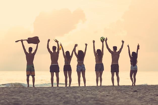 Groep vrienden die handen op het strand opheffen bij zonsondergang