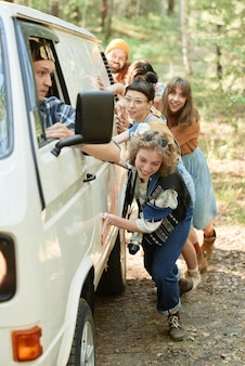 Groep vrienden die het kapotte busje duwen, ze hebben een probleem tijdens hun reizen