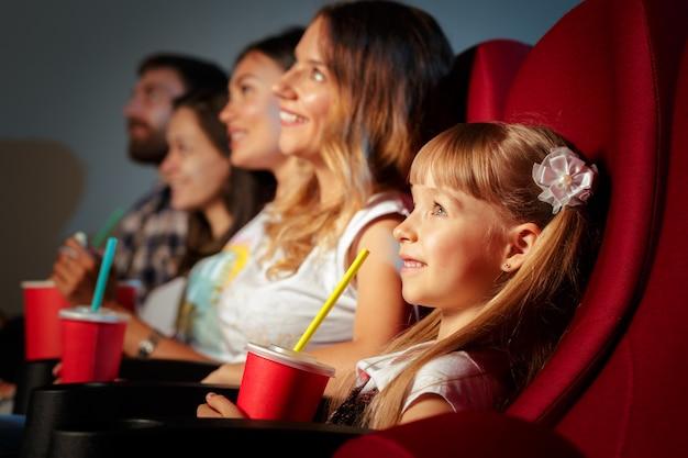 Groep vrienden die in bioscoop met popcorn en dranken zitten
