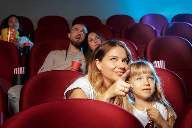 Groep vrienden die in bioscoop zitten met popcorn en dranken