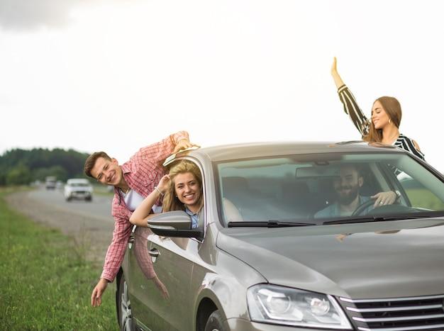 Groep vrienden die in de auto reizen die uit door open venster hangen