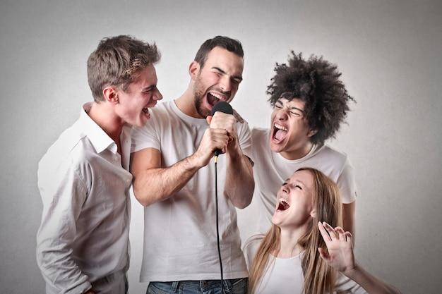 Groep vrienden die in een microfoon schreeuwen