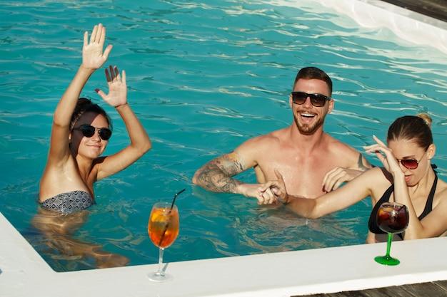 Groep vrienden die in het water bij de poolpartij dansen.