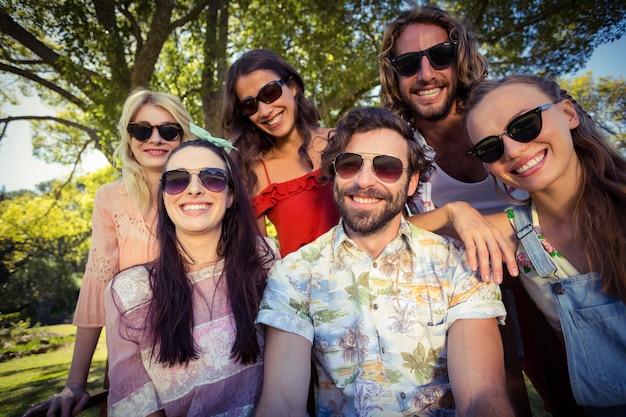 Groep vrienden die in park glimlachen