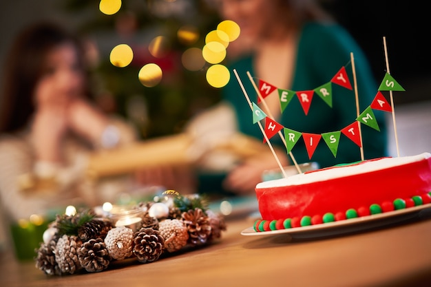 Groep vrienden die kerstmis thuis vieren en genieten van x-mass cake