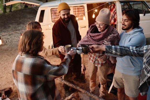 Groep vrienden die kopjes met hete thee vasthouden en samen roosteren tijdens een picknick in het bos