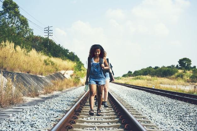 Groep vrienden die langs spoorwegsporen lopen