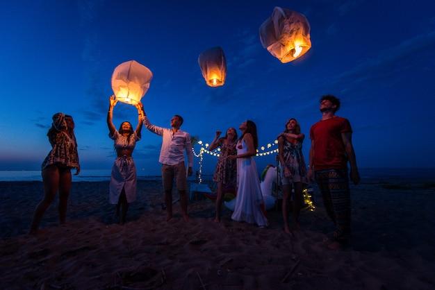 Groep vrienden die lantaarns aansteken