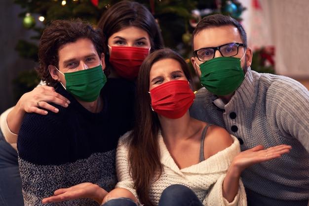 Groep vrienden die maskers dragen die kerstmis thuis vieren