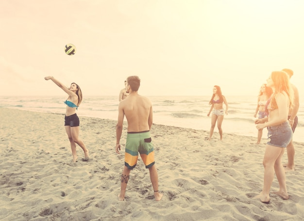 Groep vrienden die met bal op het strand spelen