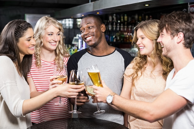 Groep vrienden die met bier en wijn roosteren