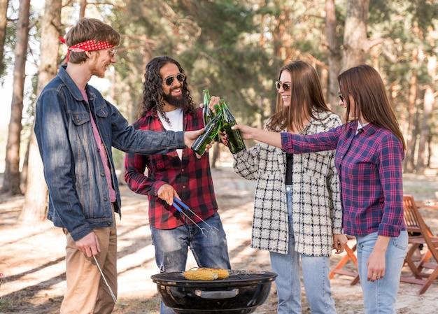 Groep vrienden die met bier over barbecue roosteren