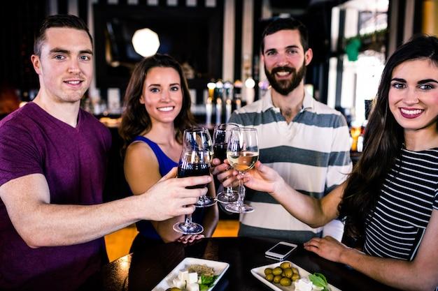 Groep vrienden die met een glas wijn in een bar roosteren