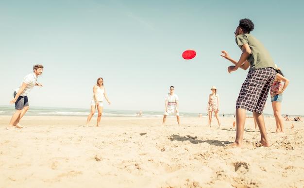 Groep vrienden die met frisbee op het strand spelen