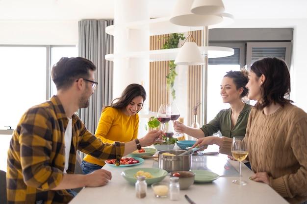 Groep vrienden die met wijn in de keuken roosteren