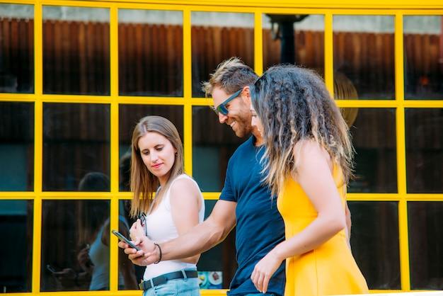 Groep vrienden die mobiele slimme telefoon met behulp van - verslavingsconcept.