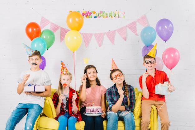 Groep vrienden die op bank met verjaardagscake zitten; ballonnen en cadeau