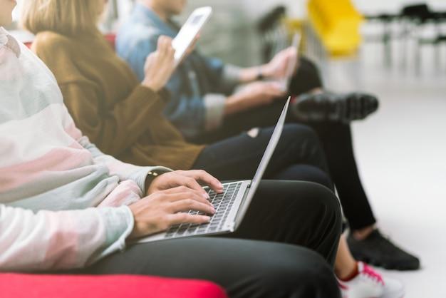 Groep vrienden die op bank zitten die laptop en smartphonetechnologie met behulp van