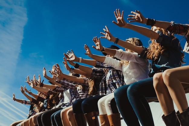 Groep vrienden die op een achtergrond van blauwe hemel op een zonnige dag zitten en hun handen voor hen uithouden. vier buiten. jongens en meisjes ondersteunen hun sportteam in competities.
