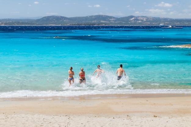 Groep vrienden die op een zonnige dag de zee in rennen