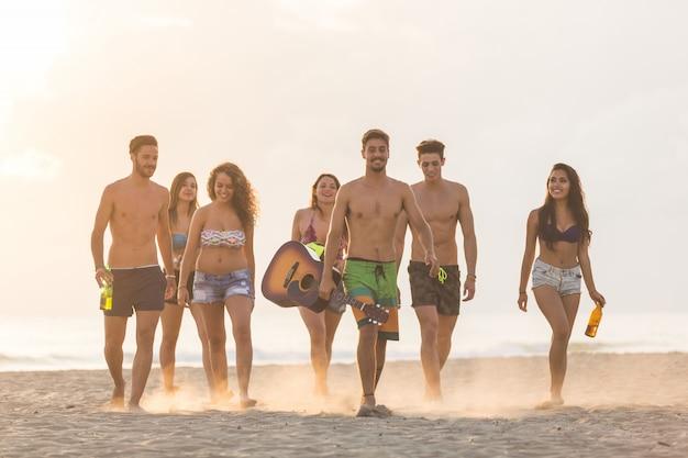 Groep vrienden die op het strand bij zonsondergang lopen.