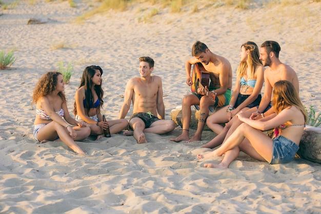 Groep vrienden die op het strand bij zonsondergang zingen.