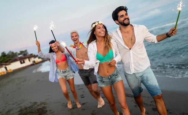 Groep vrienden die op het strand rennen en genieten van de zomervakantie