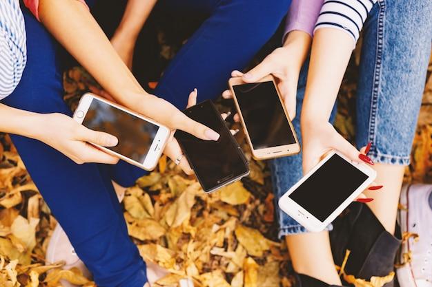 Groep vrienden die op slimme mobiele telefoons letten. handen, close-up