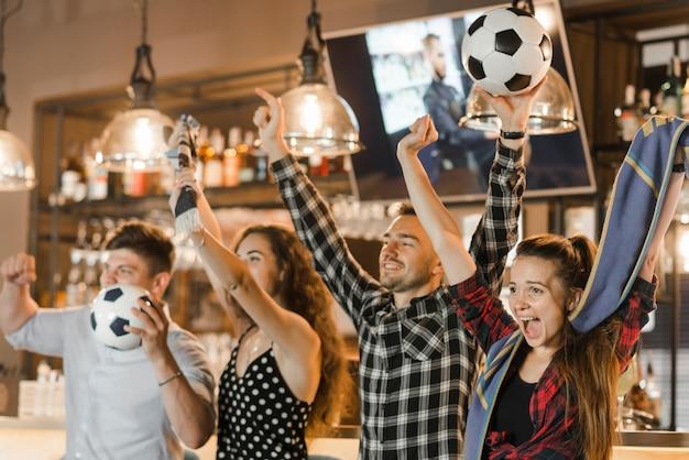 Groep vrienden die op sport letten samen vierend overwinning in de bar