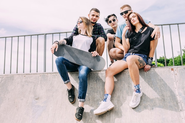 Groep vrienden die op traliewerk met skateboard zitten