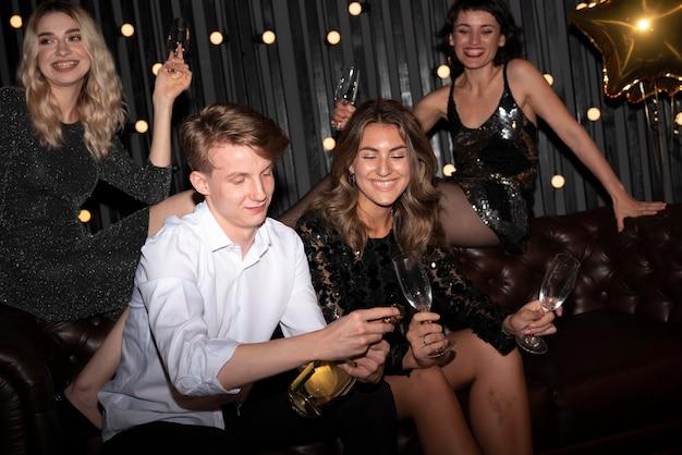 Groep vrienden die oudejaarsavond thuis vieren