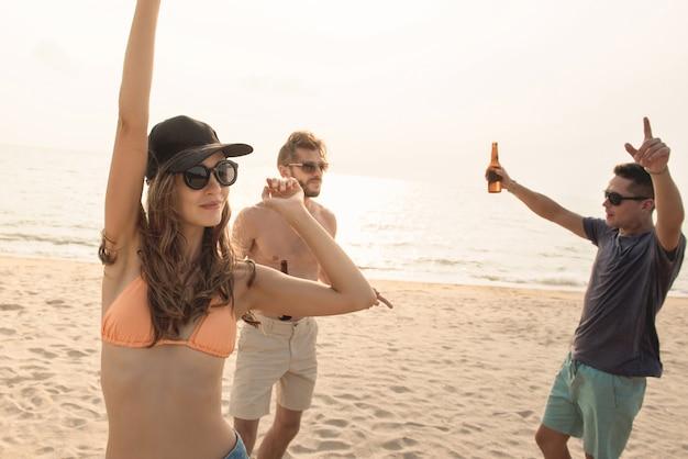 Groep vrienden die partij hebben bij het strand in de zomer