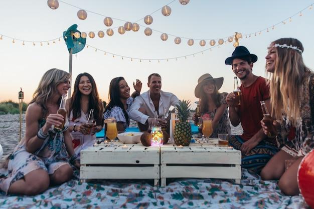 Groep vrienden die partij op het strand maken in zonsondergangtijd