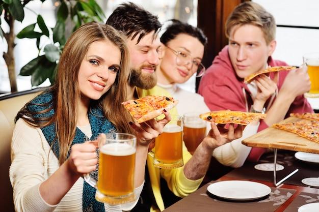 Groep vrienden die pizza eten en bier drinken bij de bar of de koffiewinkel