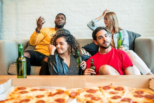 Groep vrienden die plezier hebben en bier drinken uit een fles terwijl ze samen naar een wedstrijd kijken.